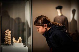 Girl looking at skeleton in display case